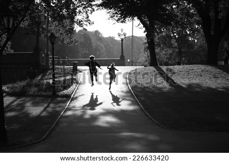 Happy teenagers jumping in the park, monochrome - stock photo