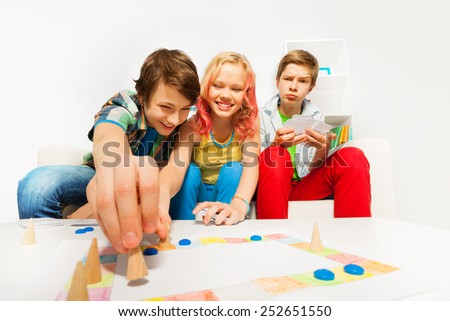 Happy teenagers play table game together at home - stock photo