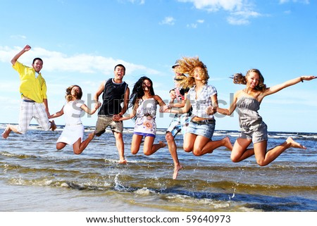 happy teenagers playing in the sea - stock photo