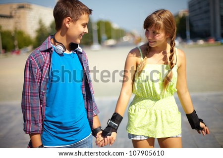 Happy teenagers spending time together in summer, girl wearing hand protection for rollers