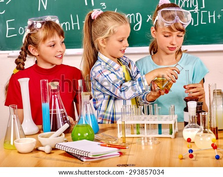 Happy teens and child holding flask in chemistry class. - stock photo