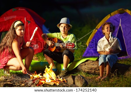 happy teens around night campfire