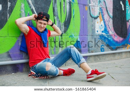 Happy teens boy sitting near painted wall and having fun