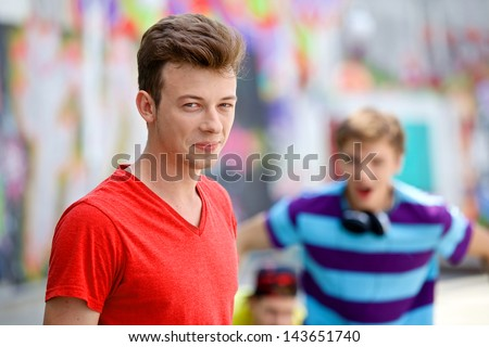 Happy teens boy with his friends by painted wall looking at camera