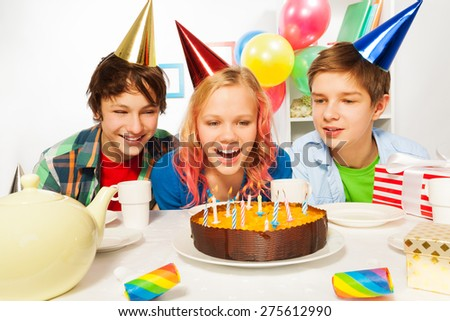 Happy teens celebrate birthday girl blow candles - stock photo