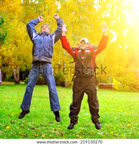 Happy Teens jumping in the Autumn Park