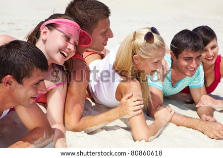 Happy teens lying on sand and posing in front of camera during summer vacation