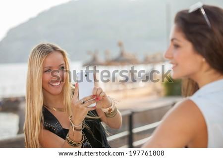Happy teens taking photos with generic smart phone - stock photo