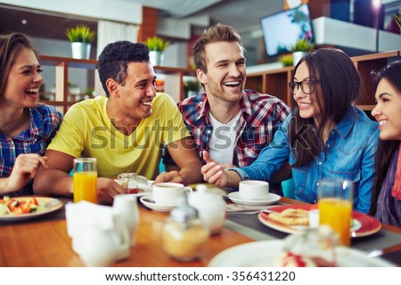 Happy teens talking during lunch in cafe - stock photo