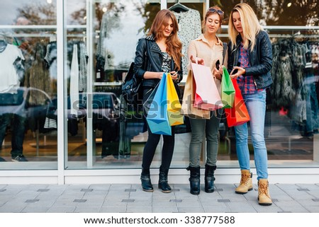 Happy teens with shopping bags are satisfied with the purchase - stock photo