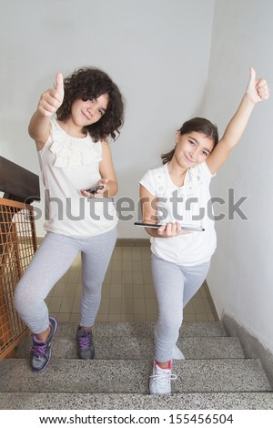 Happy ten year old twin sisters using tablet pc and smart phone - stock photo