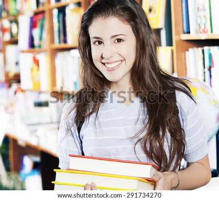 Happy tenager girl with books in library