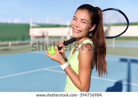 Happy tennis player girl holding tennis racket / racquet and ball on outdoor court portrait. Asian young woman fitness trainer ready for playing game match during summer. Sports activity. - stock photo