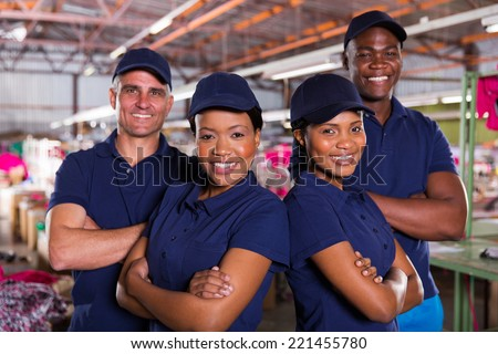 happy textile factory co-workers with arms crossed - stock photo
