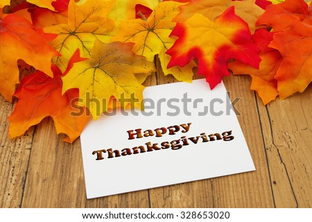 Happy Thanksgiving, Autumn Leaves on weathered grunge wood with a Happy Thanksgiving Card - stock photo