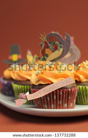Happy Thanksgiving cupcakes with turkey, feast, and pilgrim hat topper decorations against a harvest red brown background. Close up with bokeh vertical, with copy space. - stock photo