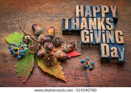 Happy Thanksgiving Day - text in vintage letterpress wood type with fall decoration (acorns, cones, leaf and vine berries) against rustic wood - stock photo