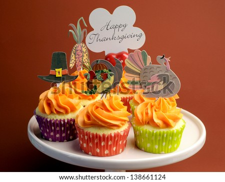 Happy Thanksgiving decorated cupcakes with turkey, pilgrim hat and corn toppers on cake stand against a brown background, with Happy Thanksgiving message. - stock photo