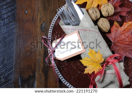 Happy Thanksgiving dining table place setting in traditional rustic country style with hessian wrapped cutlery on rustic wood background, with copy space. - stock photo