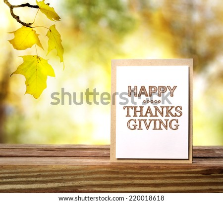 Happy Thanksgiving message card over fall leaves background - stock photo