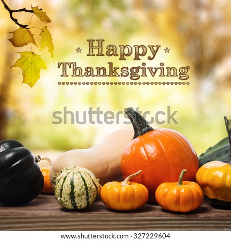 Happy Thanksgiving message with assorted pumpkins on rustic wooden boards - stock photo