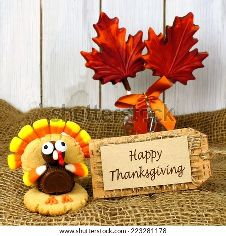 Happy Thanksgiving tag with turkey shaped cookie on burlap and wood background - stock photo