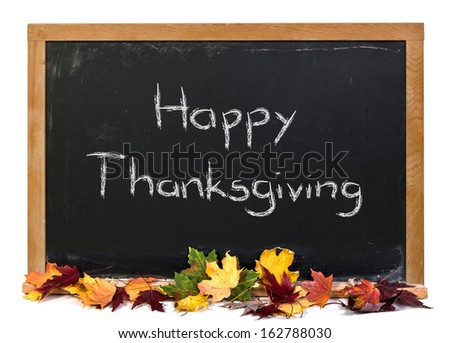 Happy Thanksgiving written in white chalk on a black chalkboard with colorful autumn leaves isolated on white - stock photo