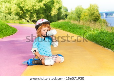 Happy thee years old boy sit with rollerblading and drink water from bottle in the park on sunny summer day - stock photo