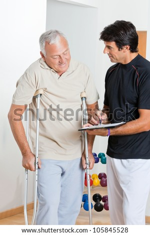 Happy therapist writing report while standing with senior man on crutches