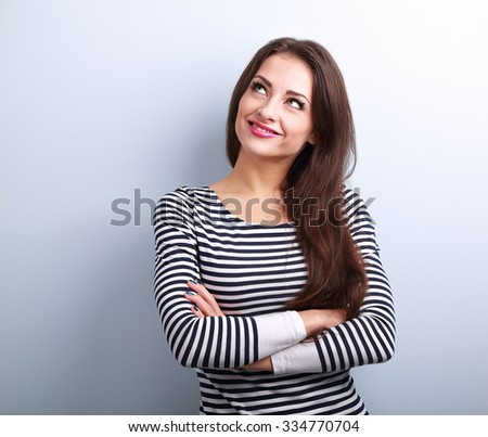 Happy thinking casual girl with folded hands looking up on blue background with empty copy space - stock photo