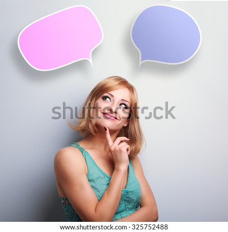 Happy thinking casual woman looking up on color speech bubbles above - stock photo
