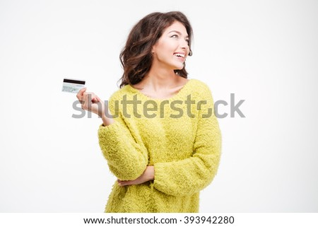 Happy thoughtful woman holding bank card isolated on a white background - stock photo