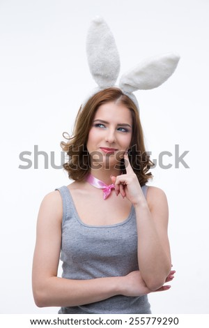 Happy thoughtful woman in rabbit ears looking away - stock photo
