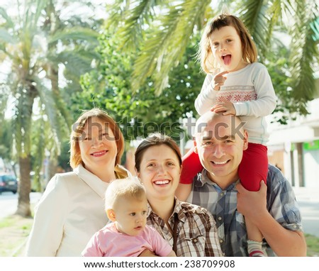 Happy three generations family  in summer street - stock photo