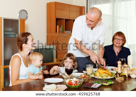 happy three generations family posing together over celebratory table