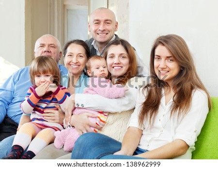 Happy three generations family sits on sofa at home