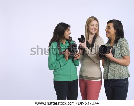 Happy three multiethnic young women holding digital cameras in studio - stock photo