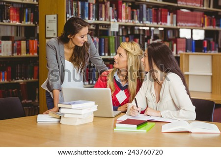 Happy three students working together in library