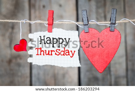 Happy Thursday on instant paper and small red hearts hanging on the clothesline. On old wood background - stock photo