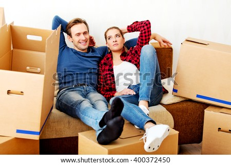 Happy tired couple sitting on couch in new home with cordboard boxes around - stock photo