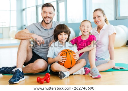 Happy to be a family. Happy sporty family bonding to each other while sitting on exercise mat together   - stock photo