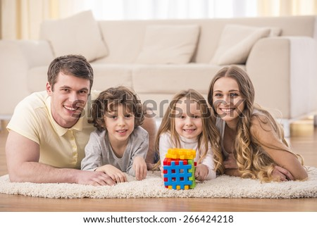 Happy to be a family. Portrait of happy family with kids in living room. - stock photo