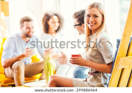 Happy to be a part of successful team. Happy young woman holding cup of coffee and looking at camera while her colleagues discussing something in the background  - stock photo