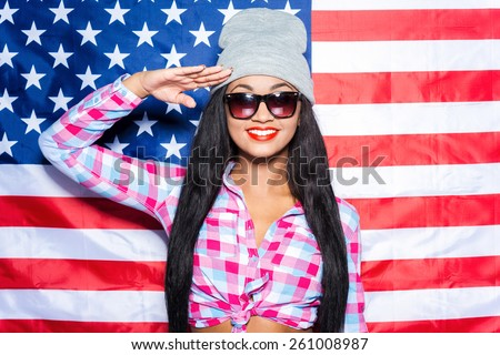 Happy to be American. Beautiful young black woman in funky clothes smiling and gesturing while standing against American flag