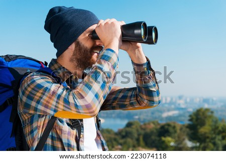 Happy to be an explorer. Handsome young bearded man carrying backpack and looking through binoculars away with smile  - stock photo