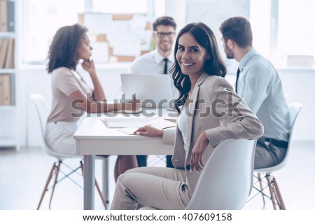 Happy to be in team. Beautiful cheerful woman looking at camera with smile while sitting at the office table with her coworkers - stock photo