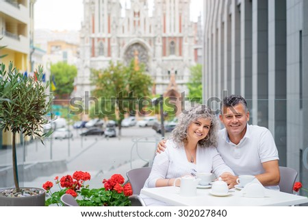 Happy to be together. Attractive elderly family couple sitting in side walk cafe. - stock photo