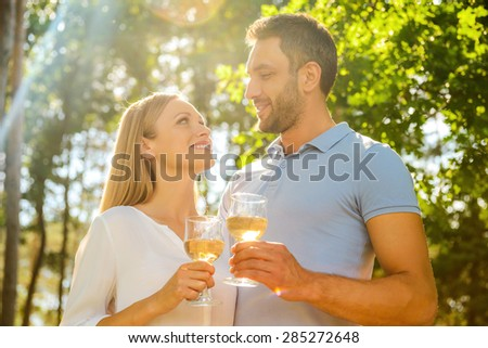 Happy to be together. Low angle view of happy young loving couple holding glasses with white wine and looking at each other with smile while standing outdoors together