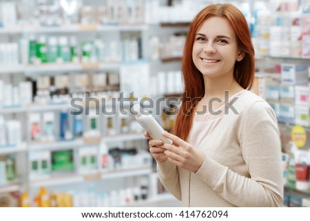 Happy to decide. Portrait of a happy pharmacy client holding a medication product looking to the camera smiling. - stock photo