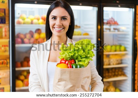 Happy to find everything I want. Beautiful young woman holding shopping bag with fruits and smiling while standing in grocery store near refrigerator   - stock photo